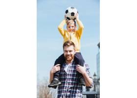 快乐的年轻父亲把他的小儿子扛在肩上_7927352
