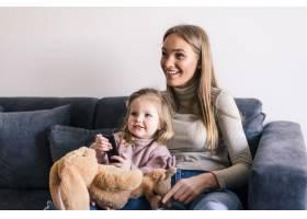 快乐的母亲带着可爱的小女儿用遥控器看电视_8471584