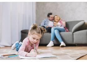 小女孩躺在地上的书上画画她慈爱的父母坐_3817126