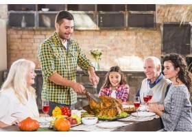 年轻人与家人在餐桌上切烤鸡_3187299