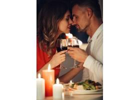 年轻女士一边吃浪漫晚餐一边亲吻她的帅哥_8081855