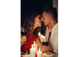 年轻女士一边吃浪漫晚餐一边亲吻她的帅哥_8081900