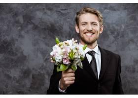 年轻帅气的新郎笑容满面手捧新娘花束_7591060