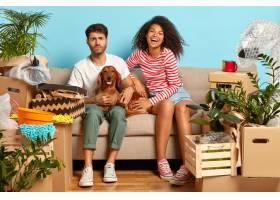 年轻多样的家庭夫妇和狗玩耍坐在空房间的_12699285