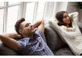 年轻夫妇在舒适的沙发上放松头后手牵手_3953856