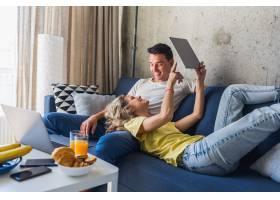 年轻夫妇坐在家里的沙发上看平板电脑在线_9699539