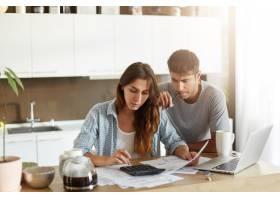 年轻夫妇检查他们的家庭预算_10113420