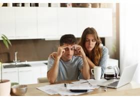 年轻夫妇检查他们的家庭预算_10113765