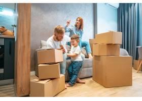 年轻幸福的家庭带着孩子一起坐在沙发上打开_6891582