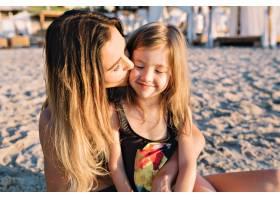 年轻漂亮的母亲和穿着黑色泳衣的小女儿在夏_12965041