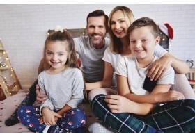 圣诞节时幸福的一家人在床上的肖像_11757073