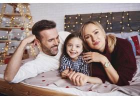 圣诞节时幸福的一家人在床上的肖像_11757122