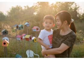在一个阳光明媚的夏日快乐的年轻母亲和她_4334626