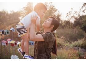 在一个阳光明媚的夏日快乐的年轻母亲和她_4334630