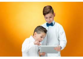 在橙色空间使用笔记本电脑的两个男孩_9479187