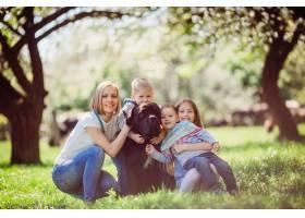 坐在草地上的母亲孩子和狗_2916336