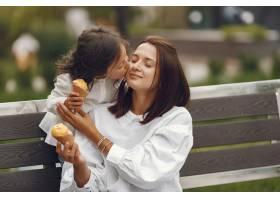 城市里的一家人小女孩吃冰激凌母亲带着_10064081