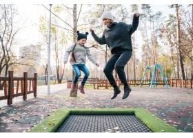 妈妈和女儿一起在秋季公园的蹦床上跳_7408567