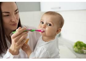 妈妈用勺子喂可爱的宝宝_9696740