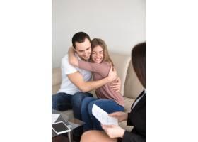 兴奋的夫妇拥抱与房地产经纪人抵押贷款投_3938444