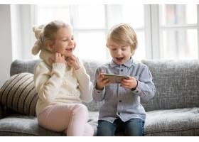 兴奋的孩子们坐在沙发上享受使用智能手机的_3953879