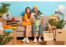 兴高采烈的年轻夫妇坐在围着箱子的沙发上_12608463