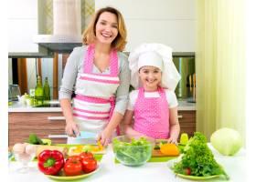 兴高采烈面带微笑的母女俩在厨房做沙拉_11599269
