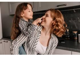 卷发年轻母亲和她欢快的小女儿在厨房的特写_12677632