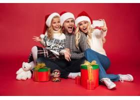 可爱快乐的年轻家庭戴着圣诞帽自拍_7440585