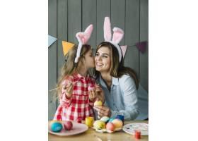 可爱的女孩在复活节彩蛋时亲吻母亲的脸颊_3836393