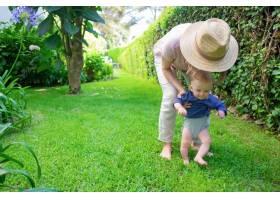 可爱的婴儿穿着蓝色衬衫在妈妈的帮助下做_9649182