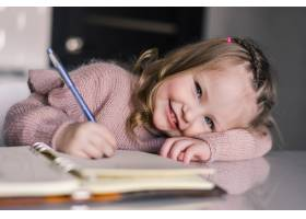 可爱的学龄前女孩在餐桌上用钢笔画画_8471508