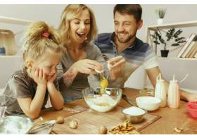 可爱的小女孩和她漂亮的父母在家里的厨房里_10521461