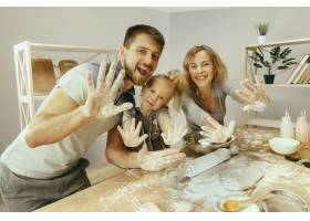 可爱的小女孩和她漂亮的父母在家里的厨房里_10542896