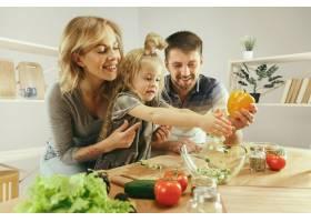 可爱的小女孩和她漂亮的父母在家里的厨房里_10542900