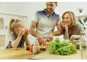 可爱的小女孩和她漂亮的父母在家里的厨房里_10542909