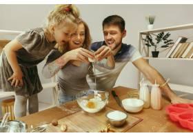 可爱的小女孩和她漂亮的父母在家里的厨房里_11161088