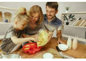 可爱的小女孩和她漂亮的父母在家里的厨房里_11161094