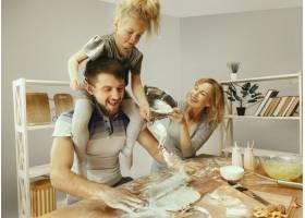 可爱的小女孩和她漂亮的父母在家里的厨房里_11161099