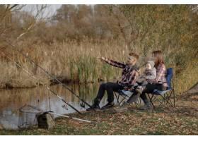 一家人早上坐在河边钓鱼_7169458