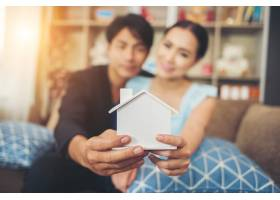 一对年轻夫妇在起居室里拿着一座白色的迷你_3398407