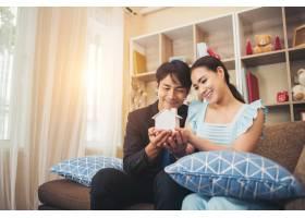 一对年轻夫妇在起居室里拿着一座白色的迷你_3398408