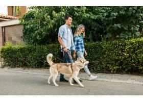 一对年轻时髦的夫妇带着狗在街上散步男人_9699445