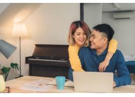 一对年轻的亚洲夫妇在管理财务使用笔记本_3521667