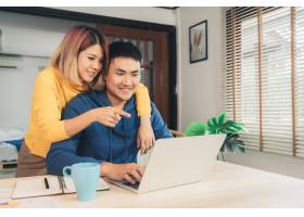 一对年轻的亚洲夫妇在管理财务使用笔记本_3521668