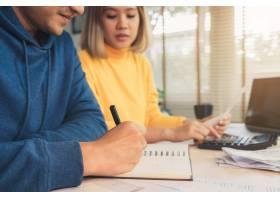 一对年轻的亚洲夫妇在管理财务使用笔记本_3521671