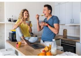 一对年轻迷人的男女早上在厨房一起吃早餐_9699585