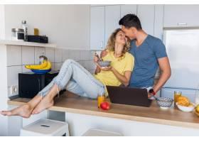 一对年轻迷人的男女早上在厨房一起吃早餐_9699597