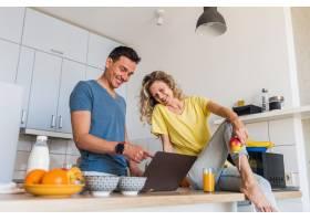 一对年轻迷人的男女早上在厨房做早餐独自_9699575