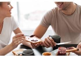 一对微笑的情侣在早上吃早餐的剪裁照片_6819630